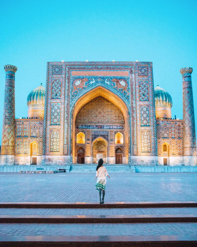 girl standing inside registan square in samarkand at night