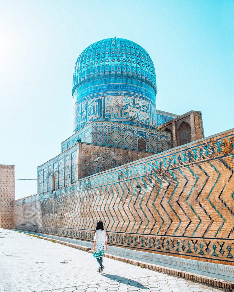 girl standing next to tile work in bibi khanym mosque in samarkand
