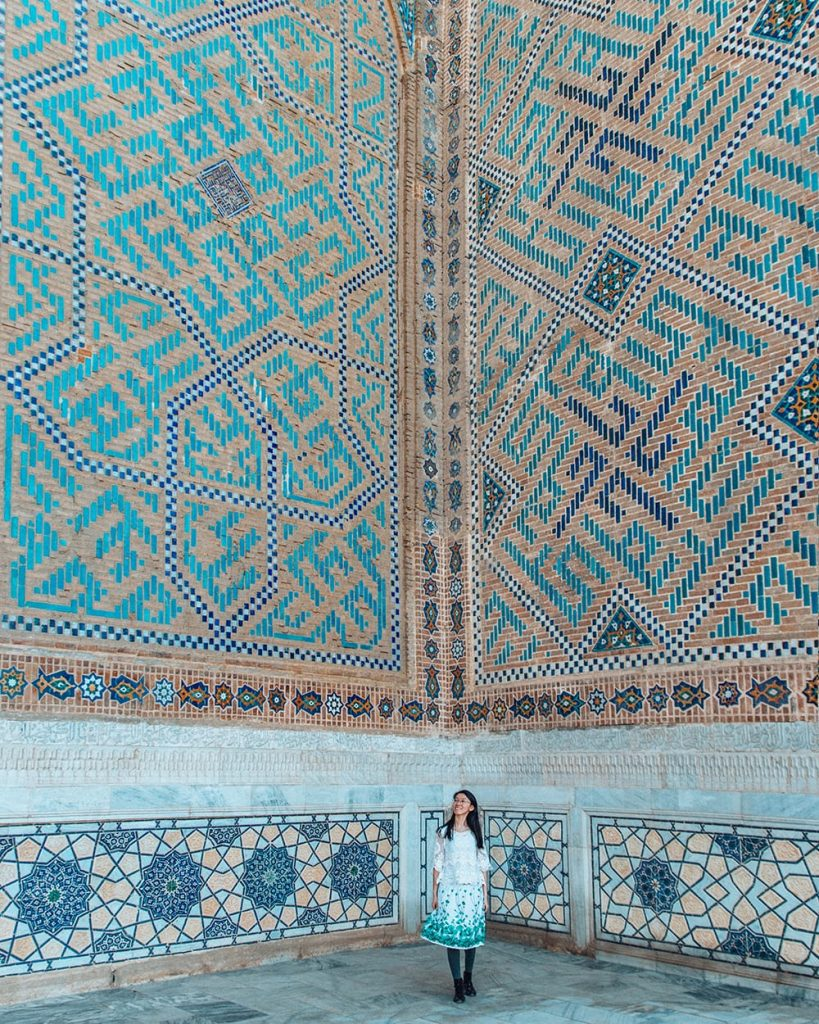 girl standing next to bibi khanym mosque tile work in samarkand