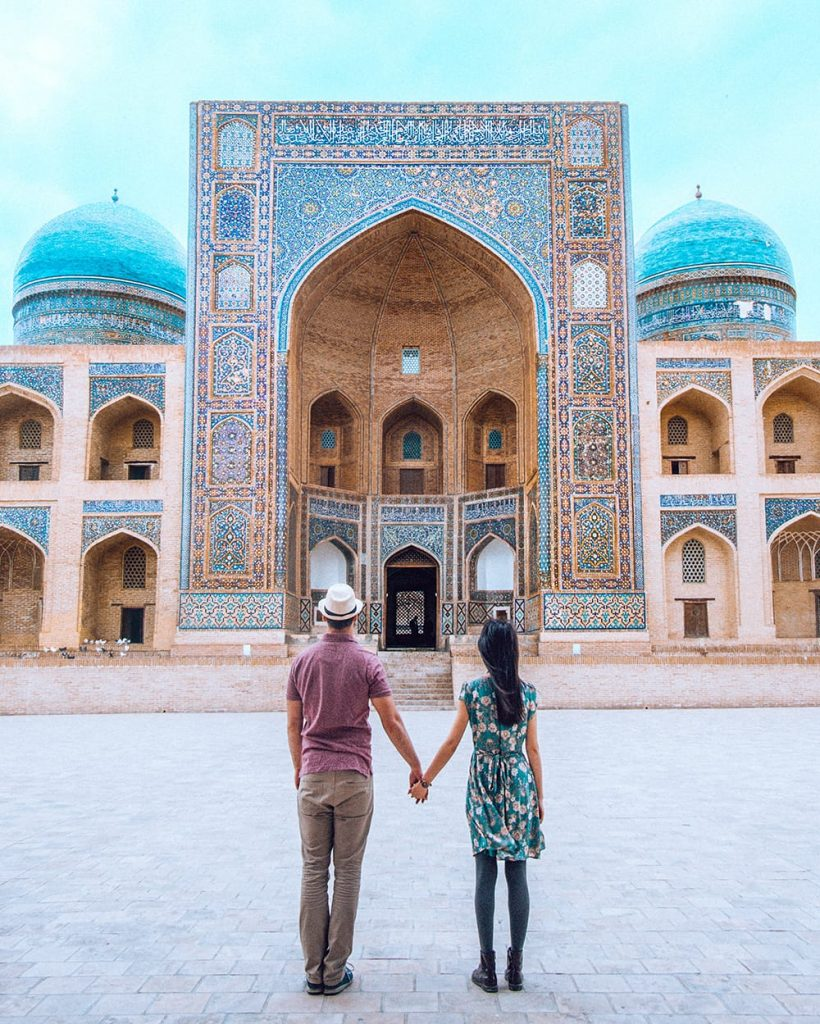 couple holding hands in po i kalyan in bukhara uzbekistan