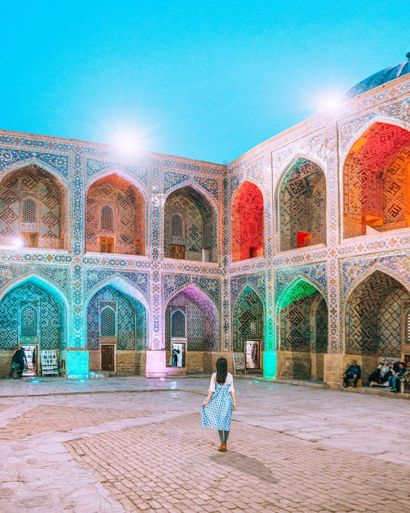 girl standing inside registan square in samarkand facing madrasah tile work at night during concert performance