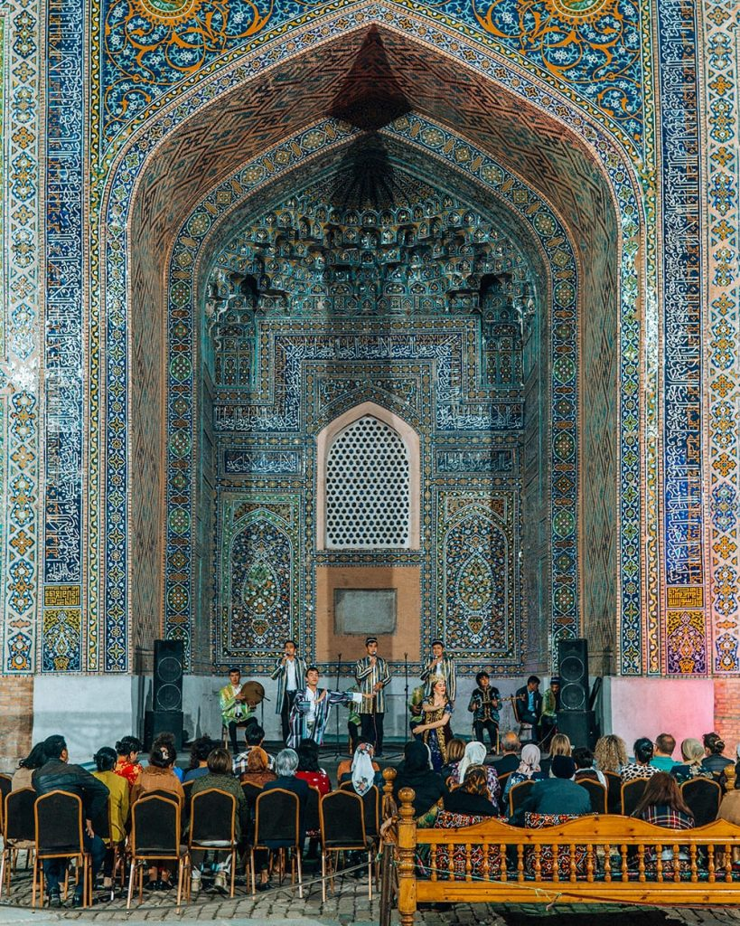 singers at concert in front of madrasah tile work in registan square at night in samarkand