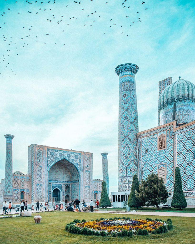 birds flying in registan square next to madrasahs