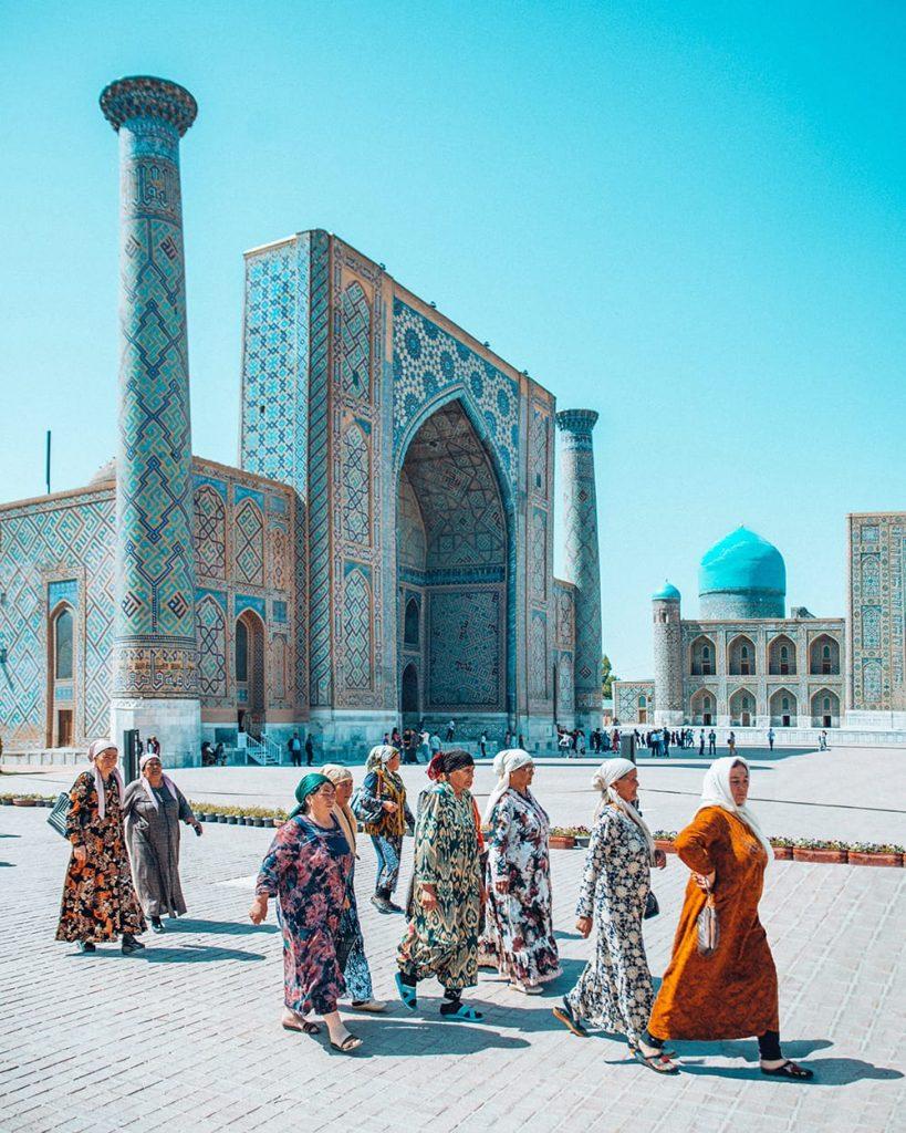 uzbekistan local ladies in colorful clothing walking inside registan square