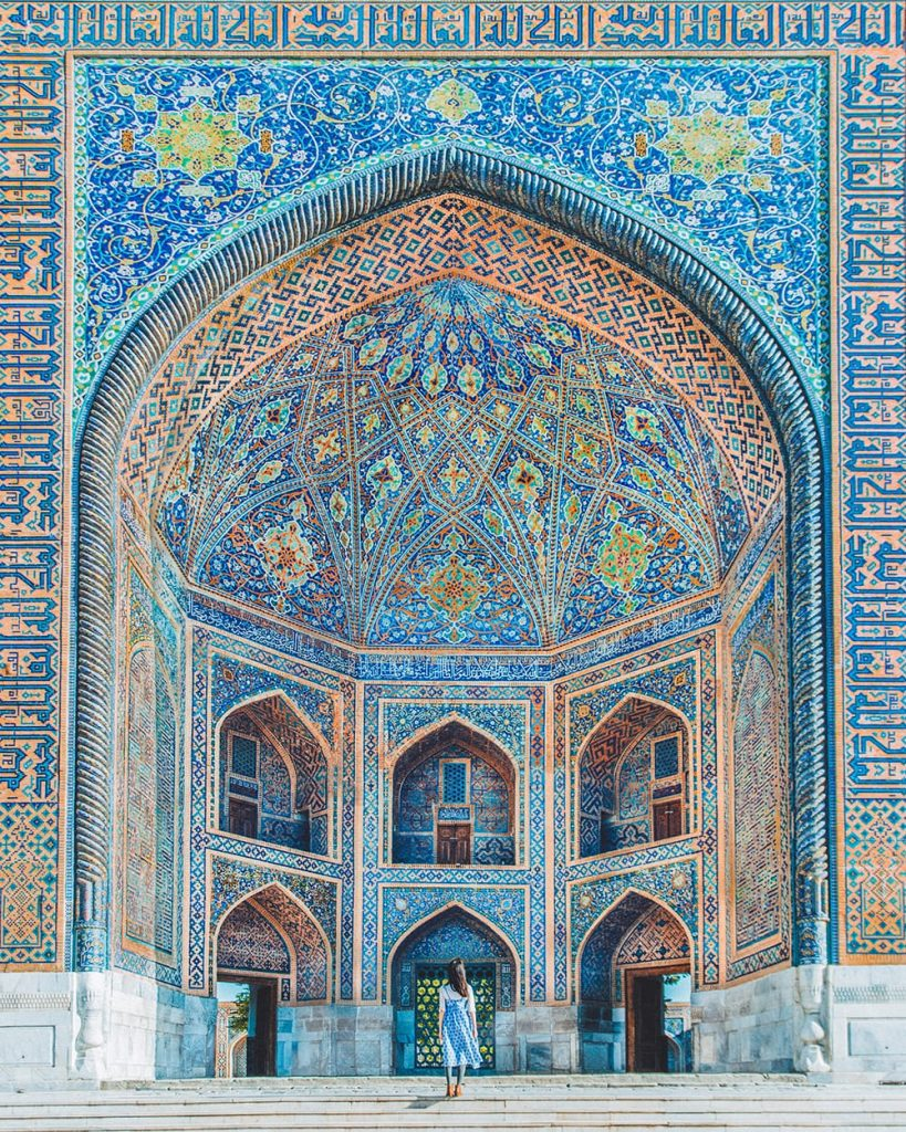 girl standing next to persian tile work of madrasah in registan square