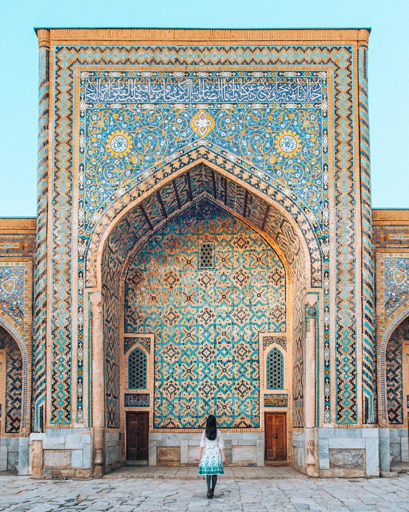 girl standing inside registan square in samarkand uzbekistan facing madrasah tile work