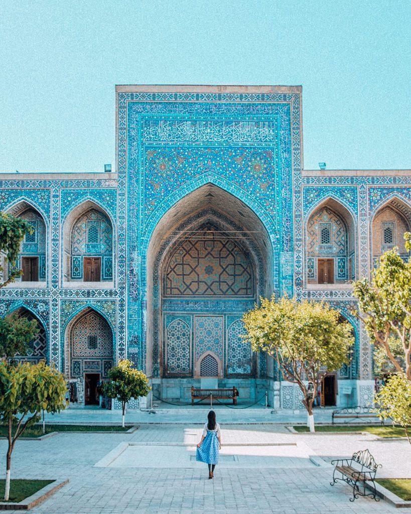 girl standing inside registan square in samarkand facing madrasah tile work