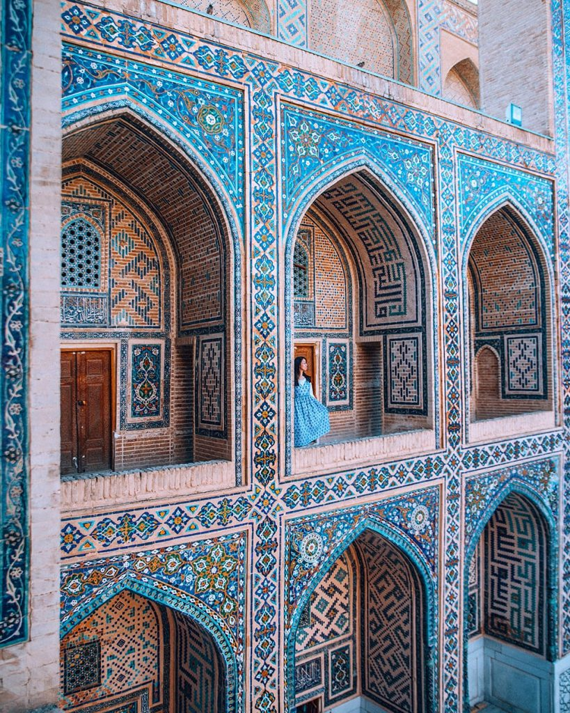 girl standing next to tile work in registan square samarkand uzbekistan