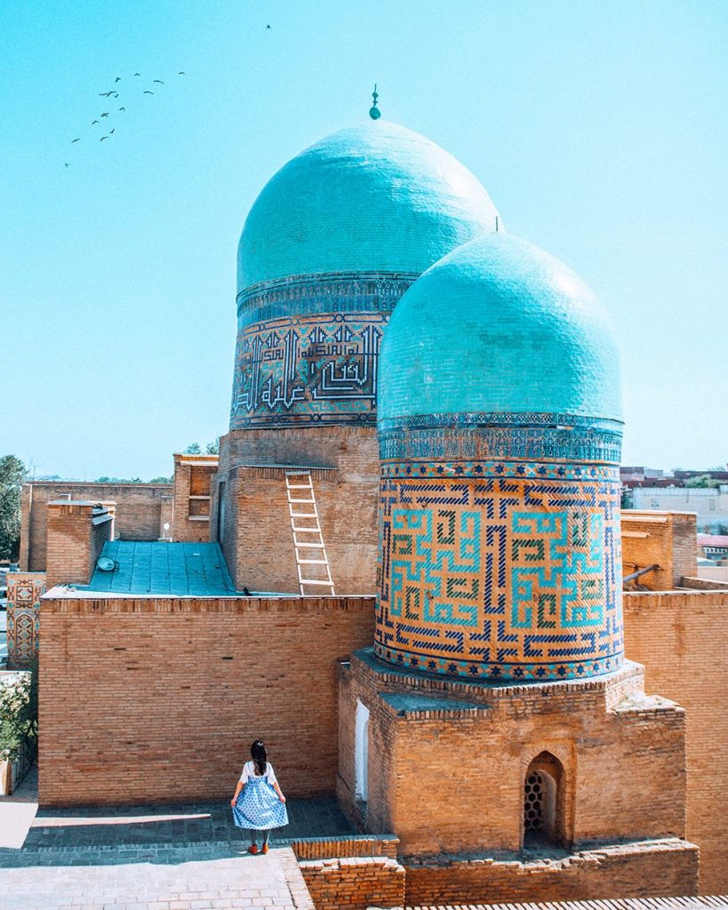uzbekistan girl standing next to architecture of shah i zinda mausoleums