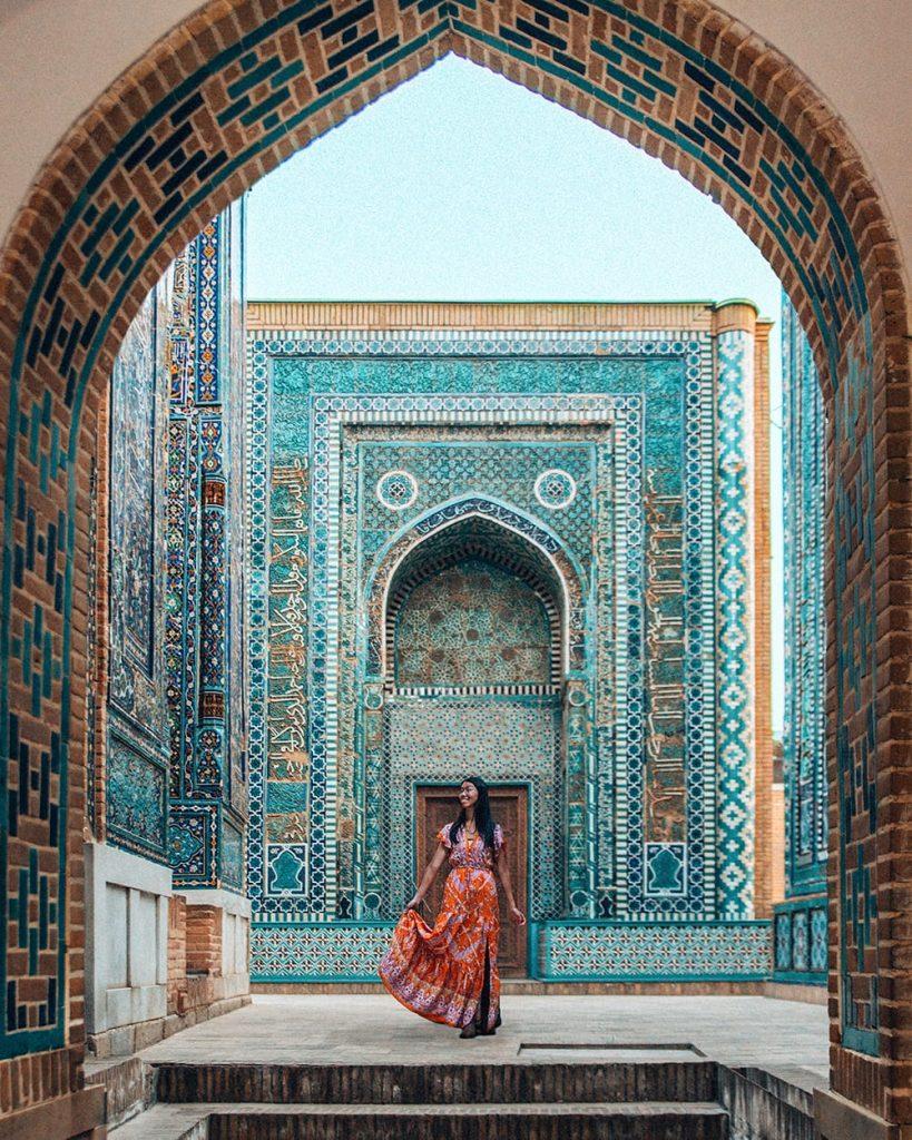 girl standing next to tile work in shah i zinda mausoleum in uzbekistan