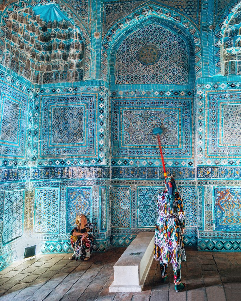 lady cleaning tile work walls of mausoleum in shah i zinda samarkand