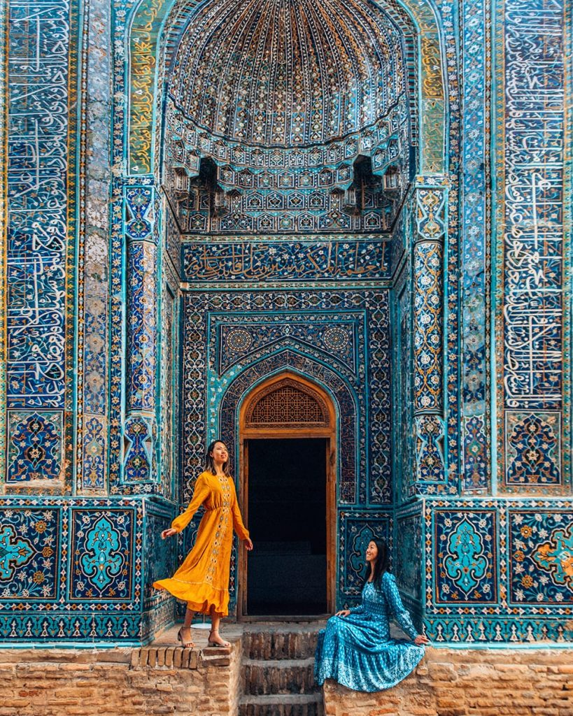 two girls standing next to tile work in shah i zinda samarkand