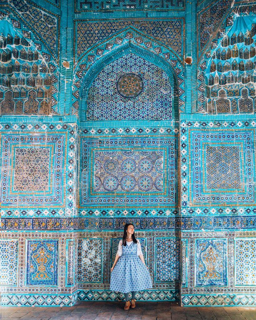 girl standing next to tile work in shah i zinda samarkand