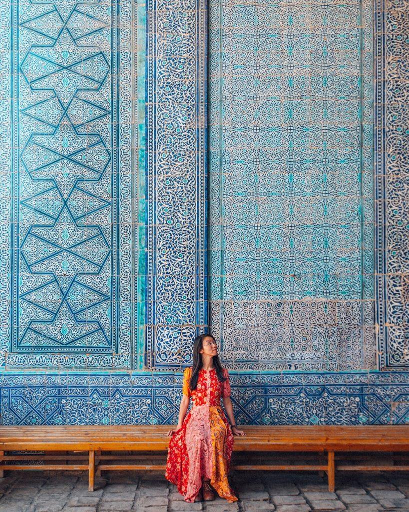 girl sitting next to tile work of tash hauli palace in uzbekistan