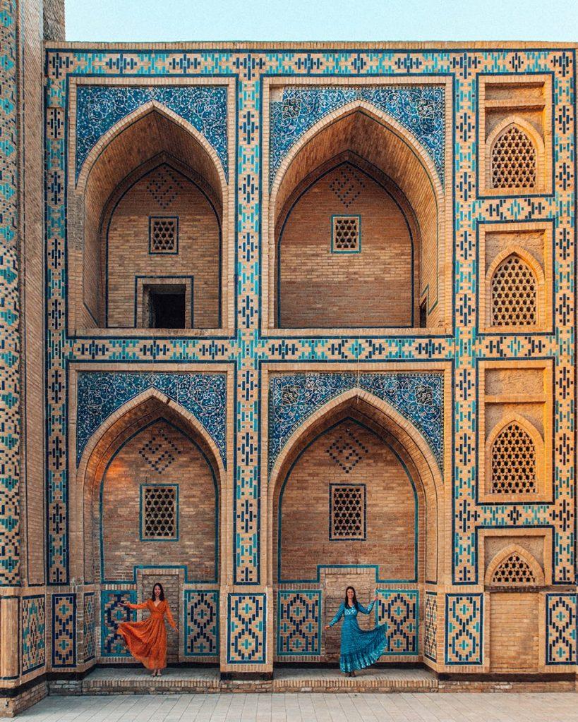girls standing at ulugh beg madrasah in bukhara uzbekistan