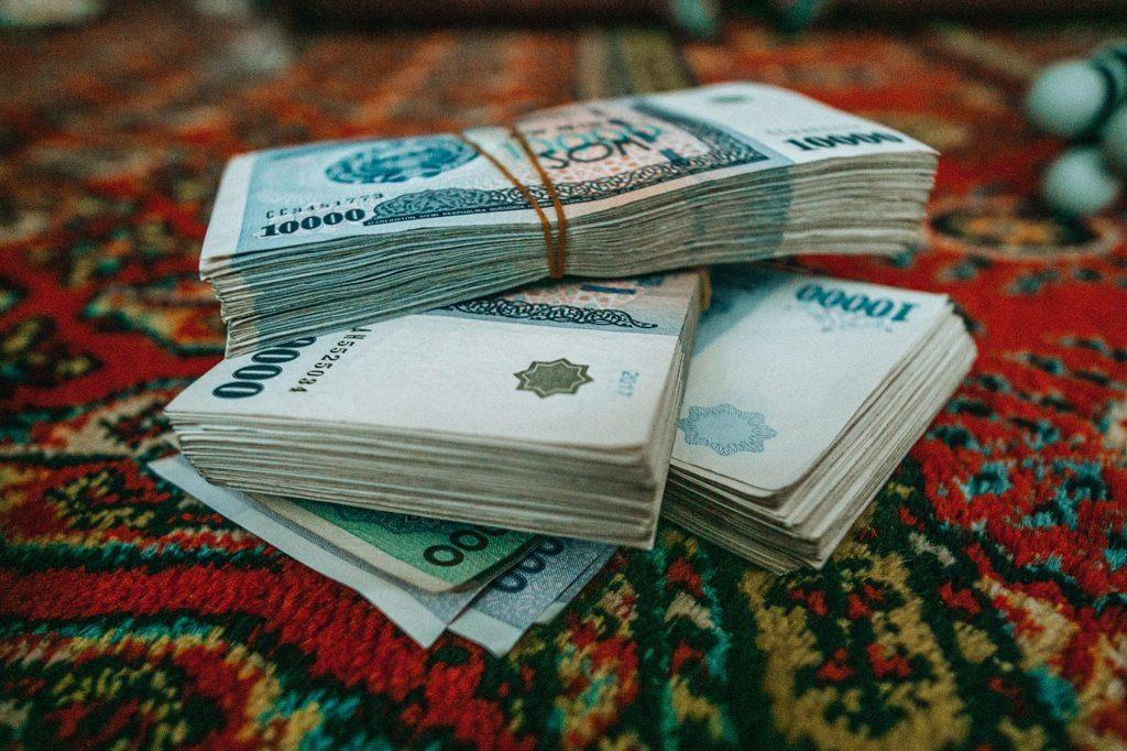 stack of cash money uzbek som on red table