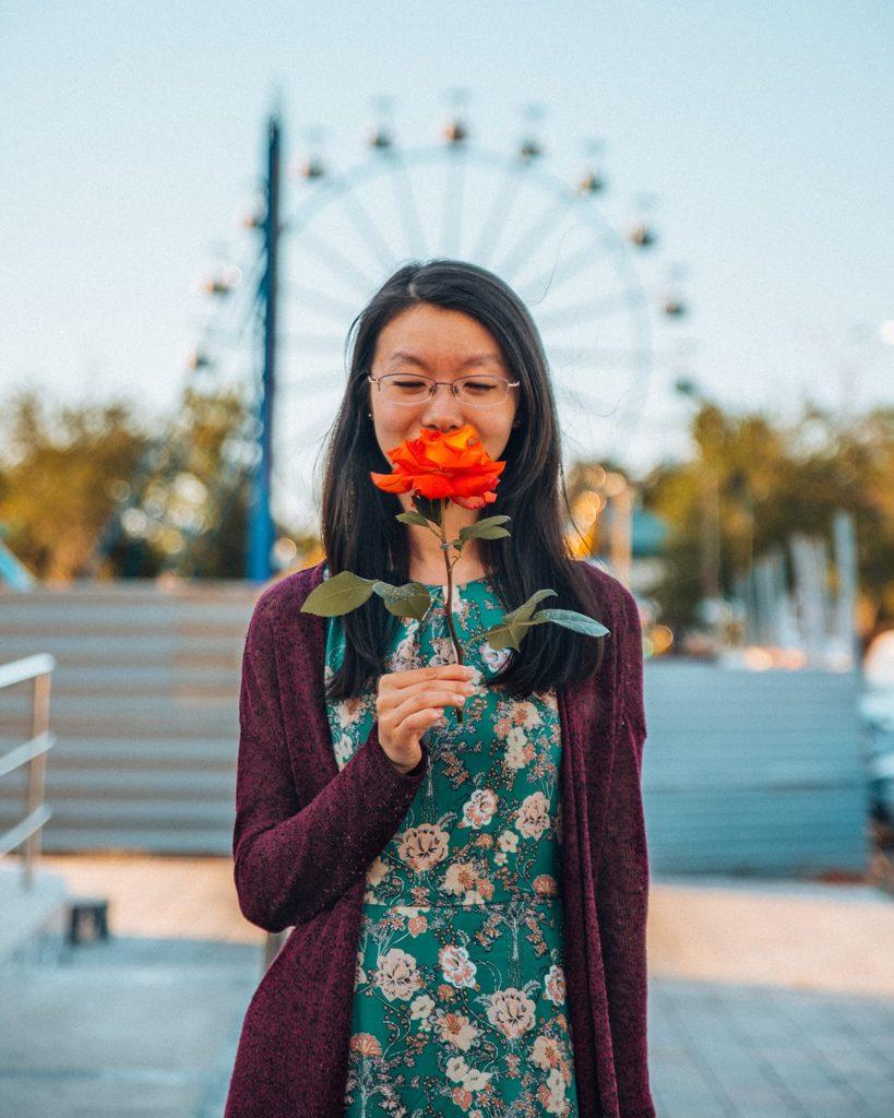 girl holding flower standing in front of ferris wheel