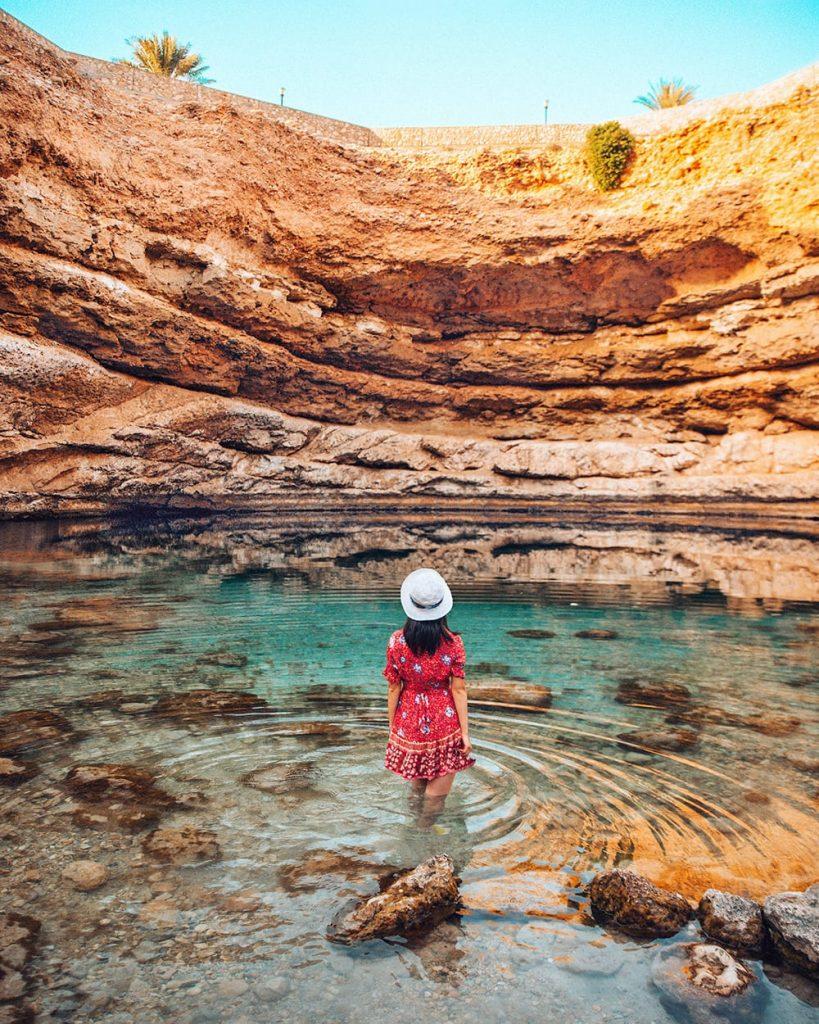 girl standing inside bimmah sinkhole