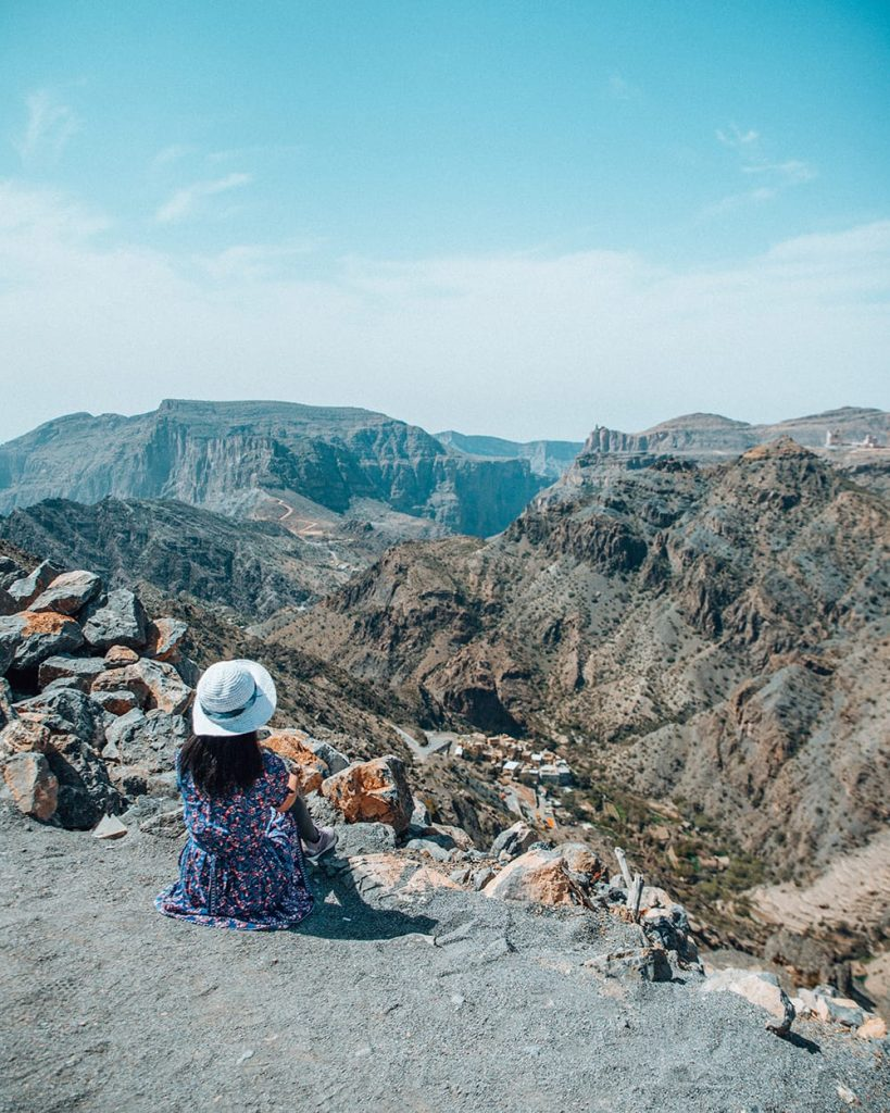 girl sitting by canyons in jebel akhdar mountain region of oman