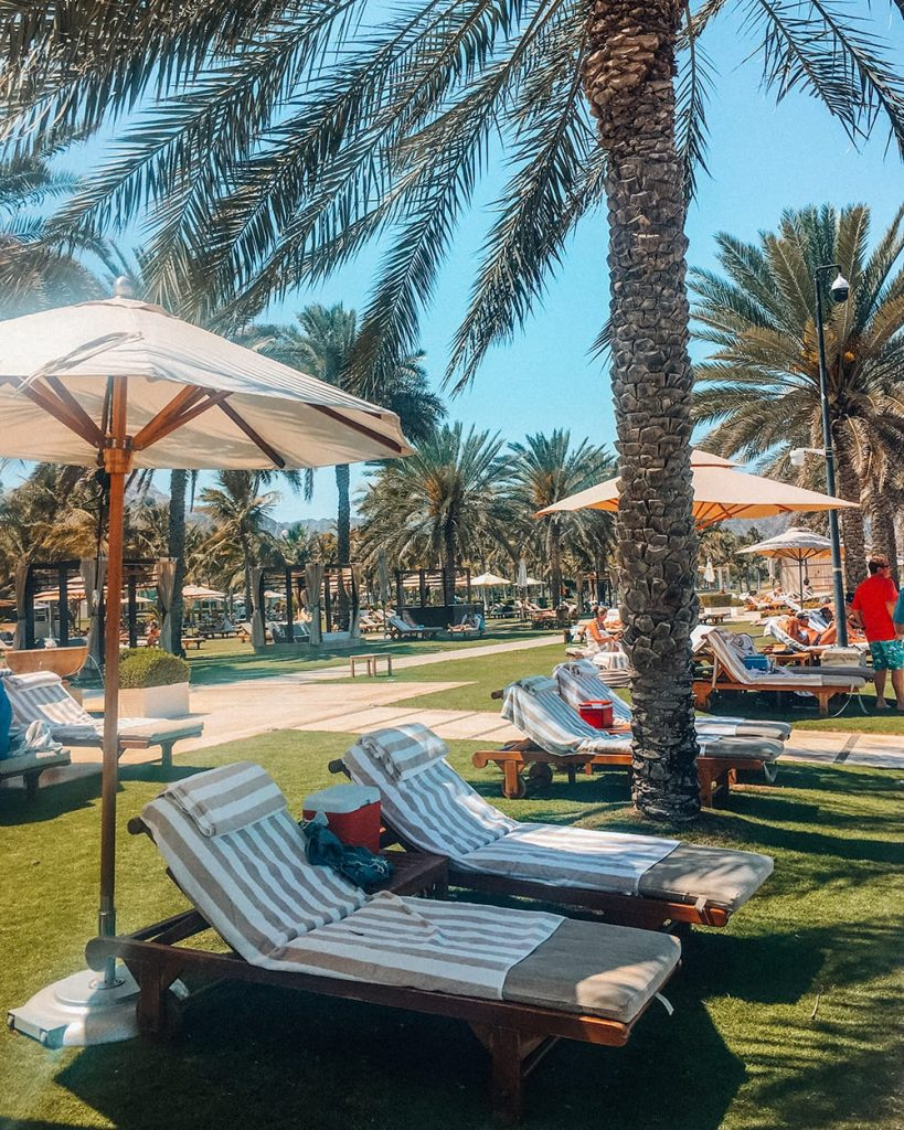al bustan palace hotel beachfront with beach beds and palm trees