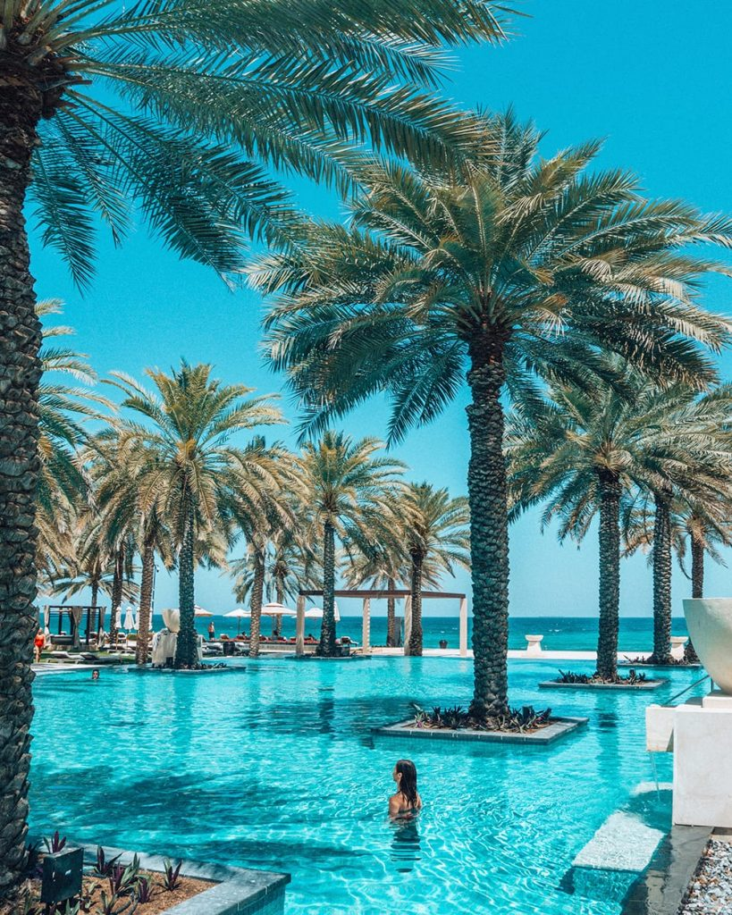 al bustan palace hotel pool with palm trees