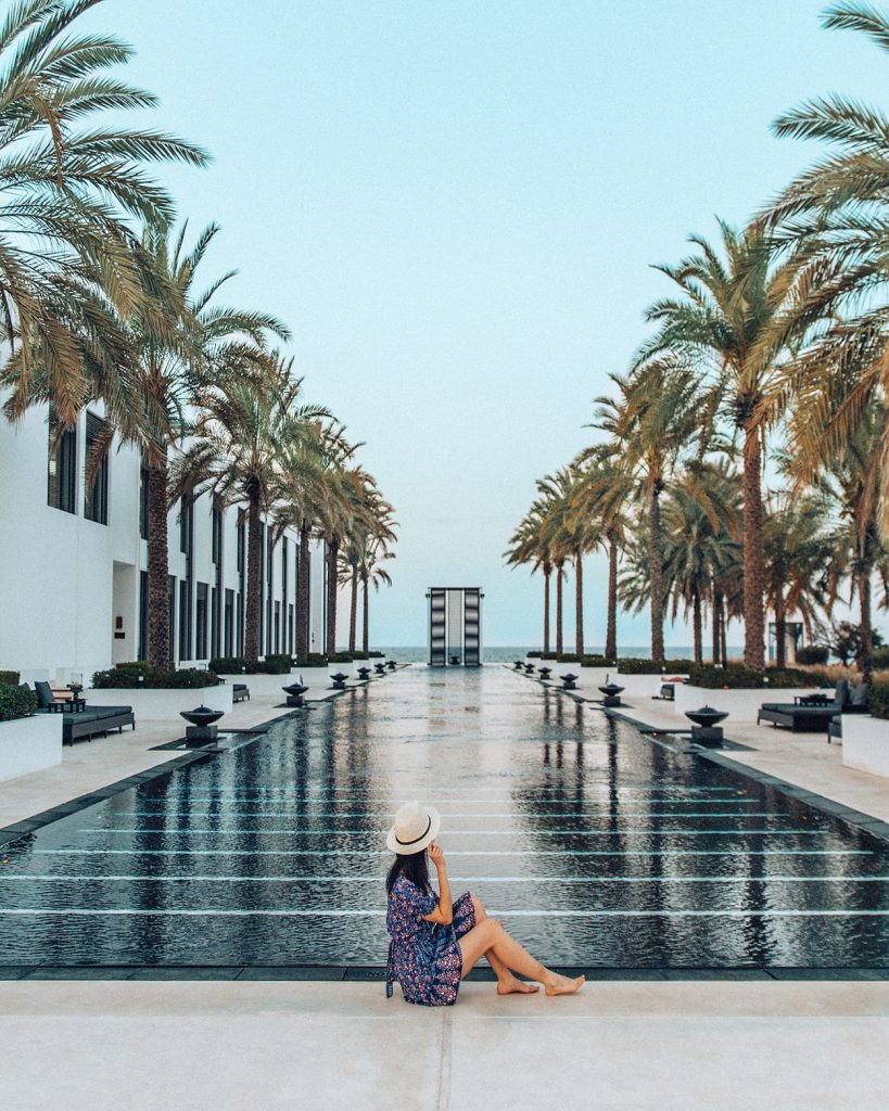 girl sitting by the long pool at the chedi muscat