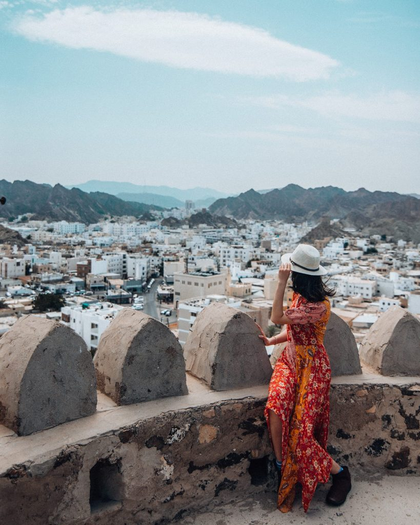 girl sitting on mutrah fort in muscat during an oman road trip