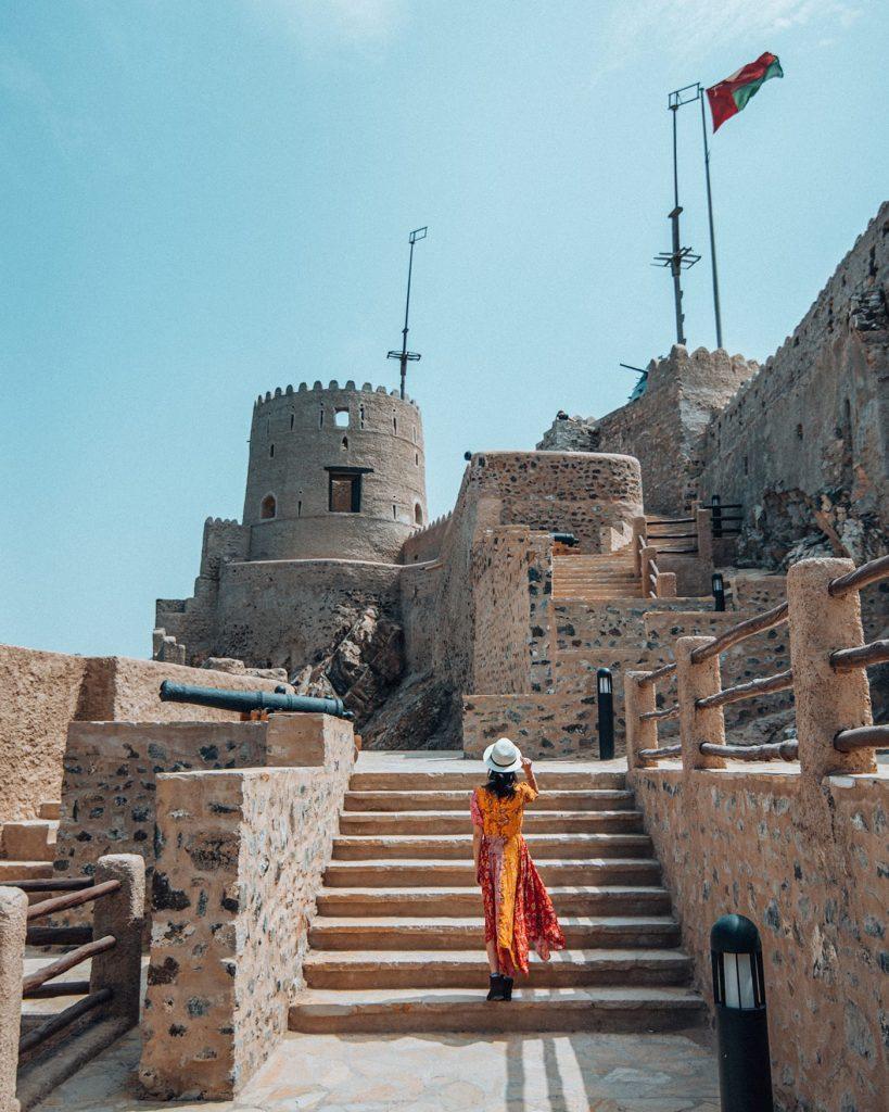 girl walking towards mutrah fort in muscat