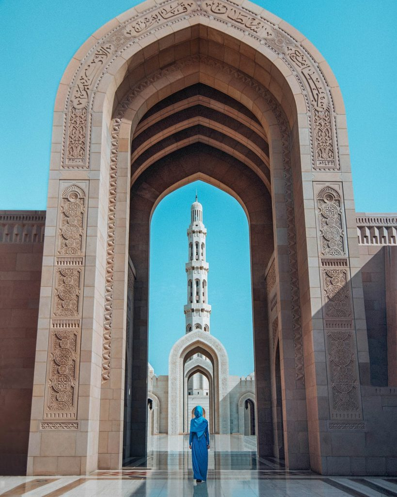 girl standing in sultan qaboos grand mosque in muscat oman