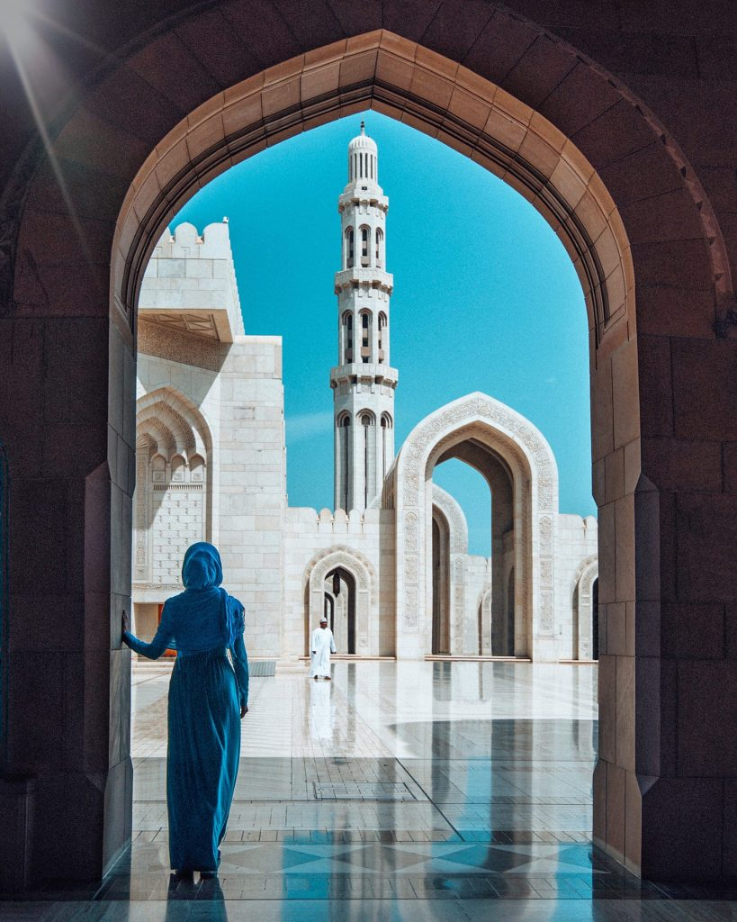 girl standing inside sultan qaboos grand mosque in muscat