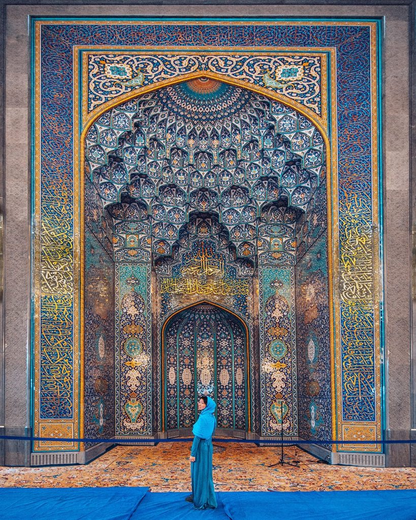 girl standing inside sultan qaboos grand mosque next to persian tiles