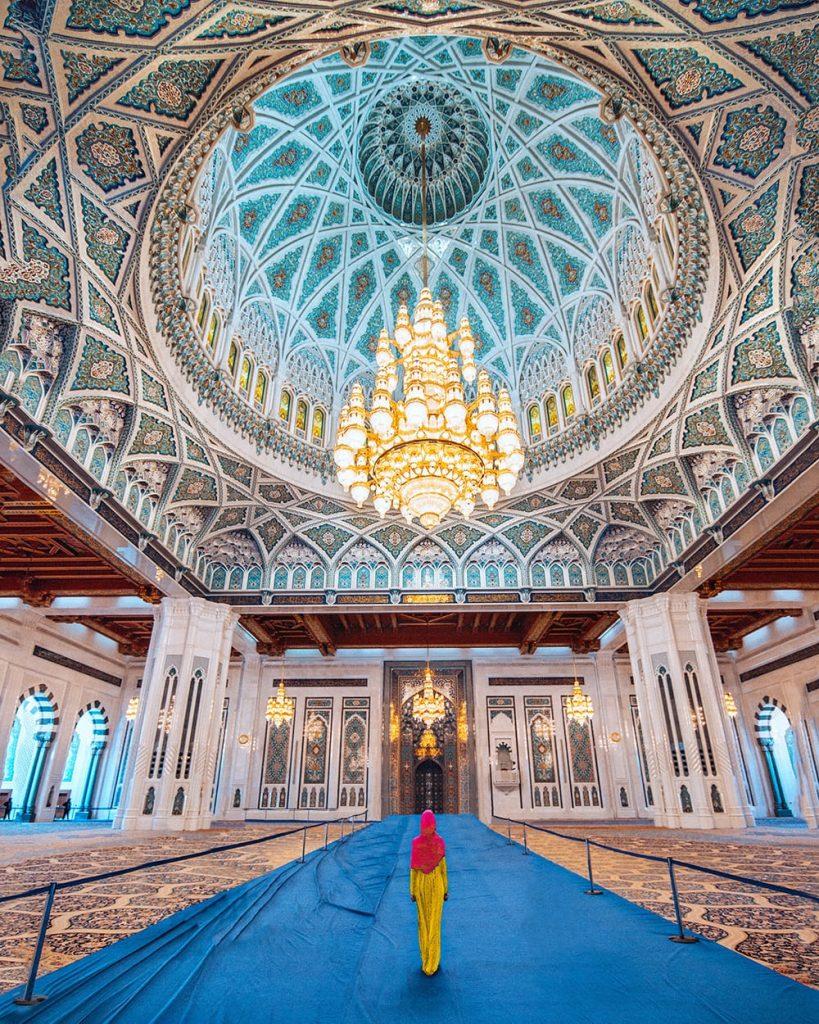 girl walking inside sultan qaboos grand mosque underneath gigantic chandelier
