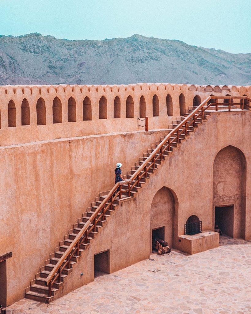 girl climbing up stairs of nizwa fort