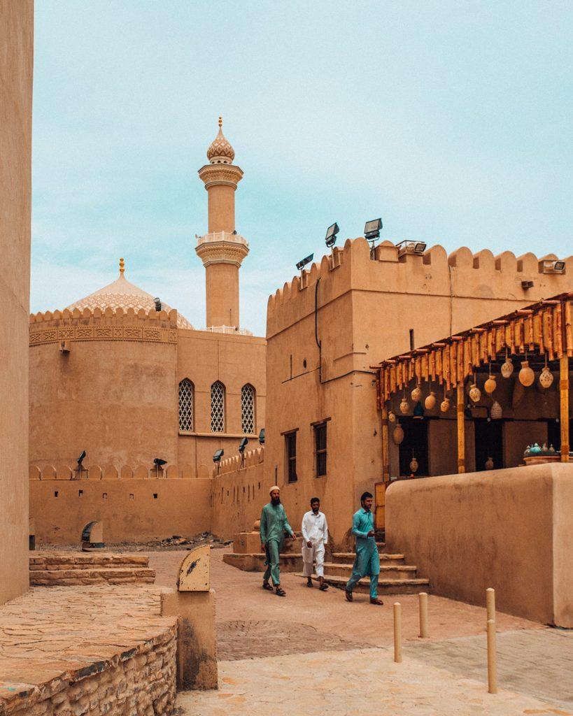 men walking near nizwa fort in oman