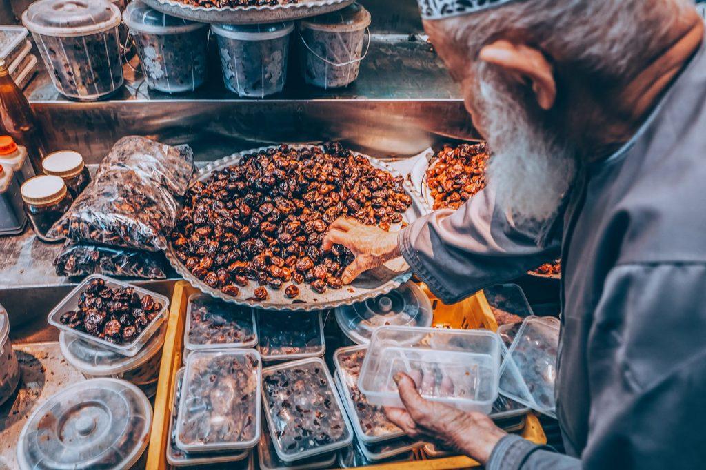 man picking up dates at a market