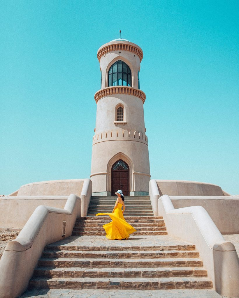 girl twirling a yellow dress in front of al ayjah lighthouse in sur middle east