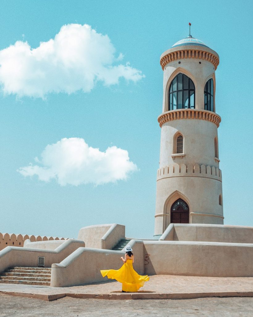 girl in a yellow dress at a lighthouse in sur