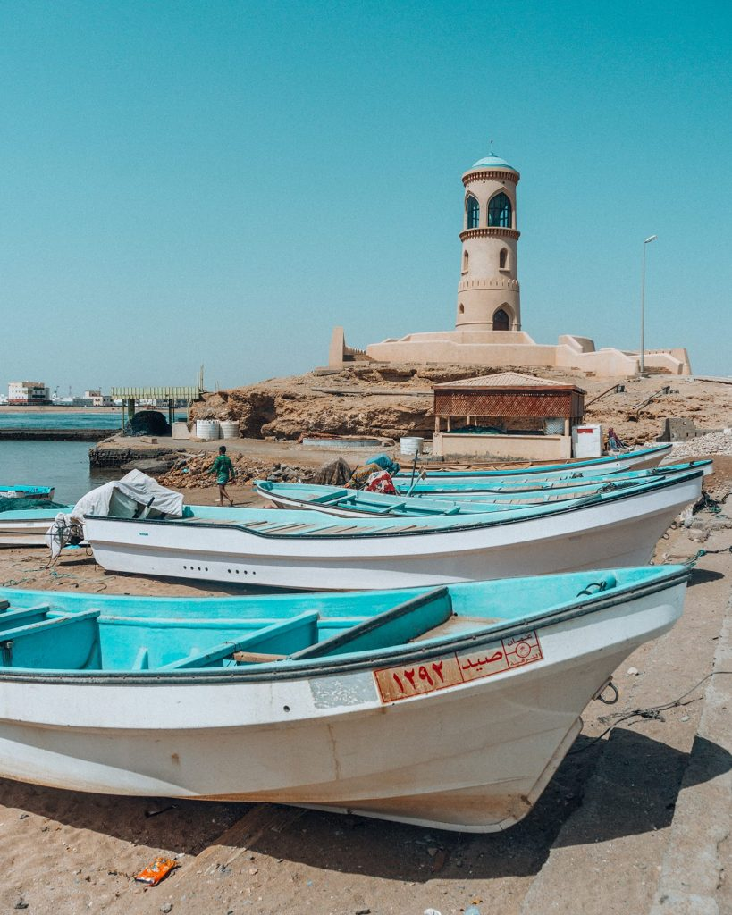 boats in front of al ayjah lighthouse in sur middle east