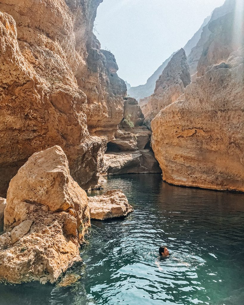 girl swimming in pool in wadi shab next to canyons