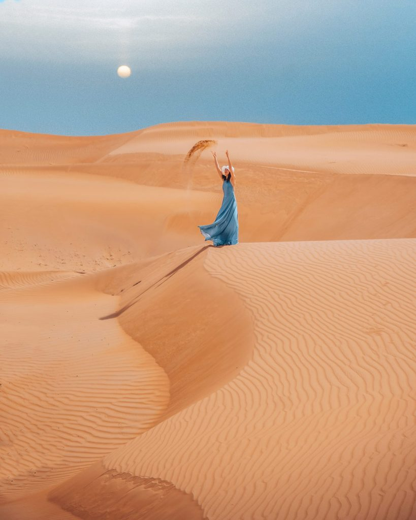girl on wahiba sands desert during sunset