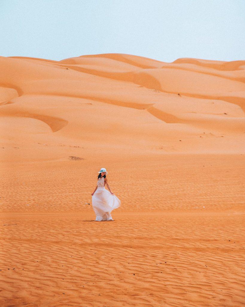 girl in a white dress on wahiba sands desert