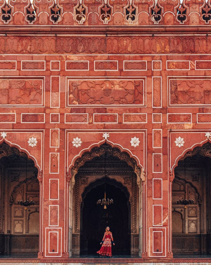 girl standing in front of red tiles of badshahi mosque in lahore pakistan