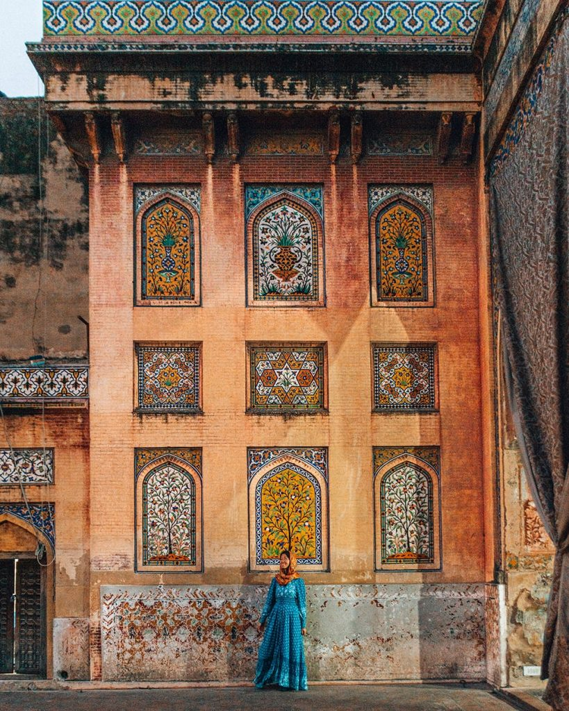 girl standing in front of masjid wazir khan mosque in lahore pakistan