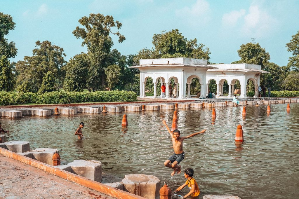 children playing and swimming inside a garden pool called shalimar bagh in lahore pakistan