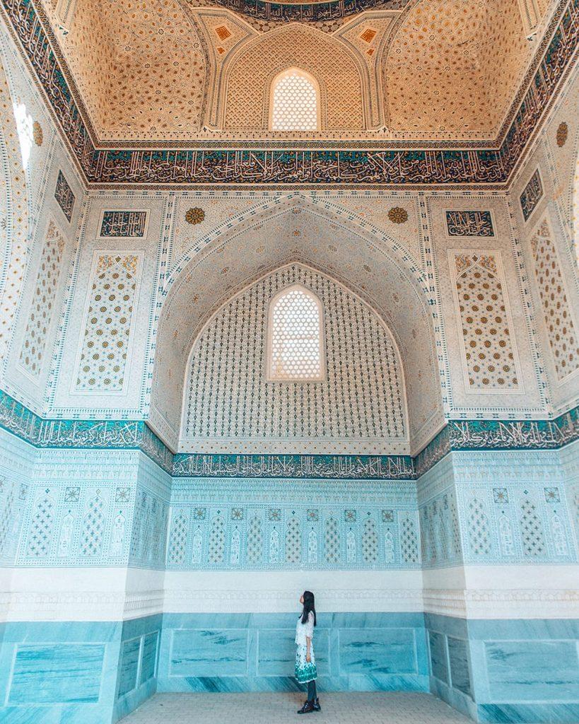 uzbekistan girl standing inside bibi khanym mosque next to tile work
