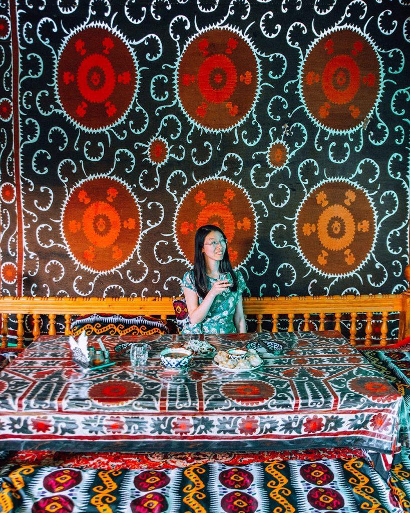 uzbekistan girl sitting at stylish restaurant with table decorations
