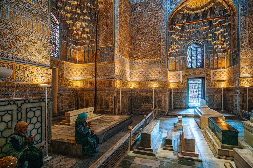 lady praying inside gur-e-amir mausoleum uzbekistan