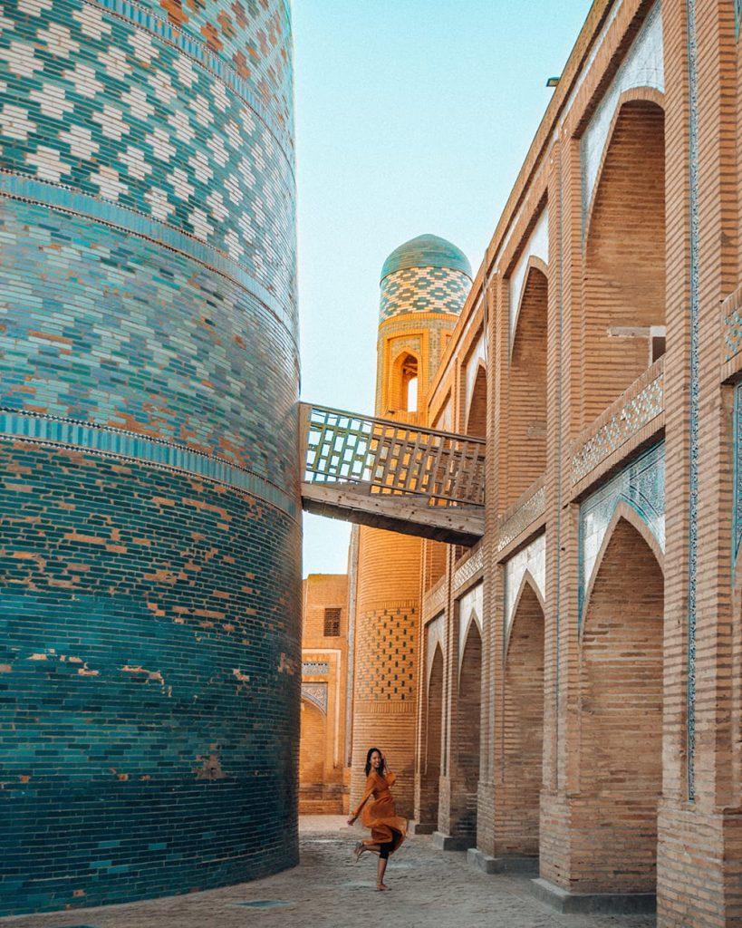 girl standing next to kalta minor minaret in khiva uzbekistan