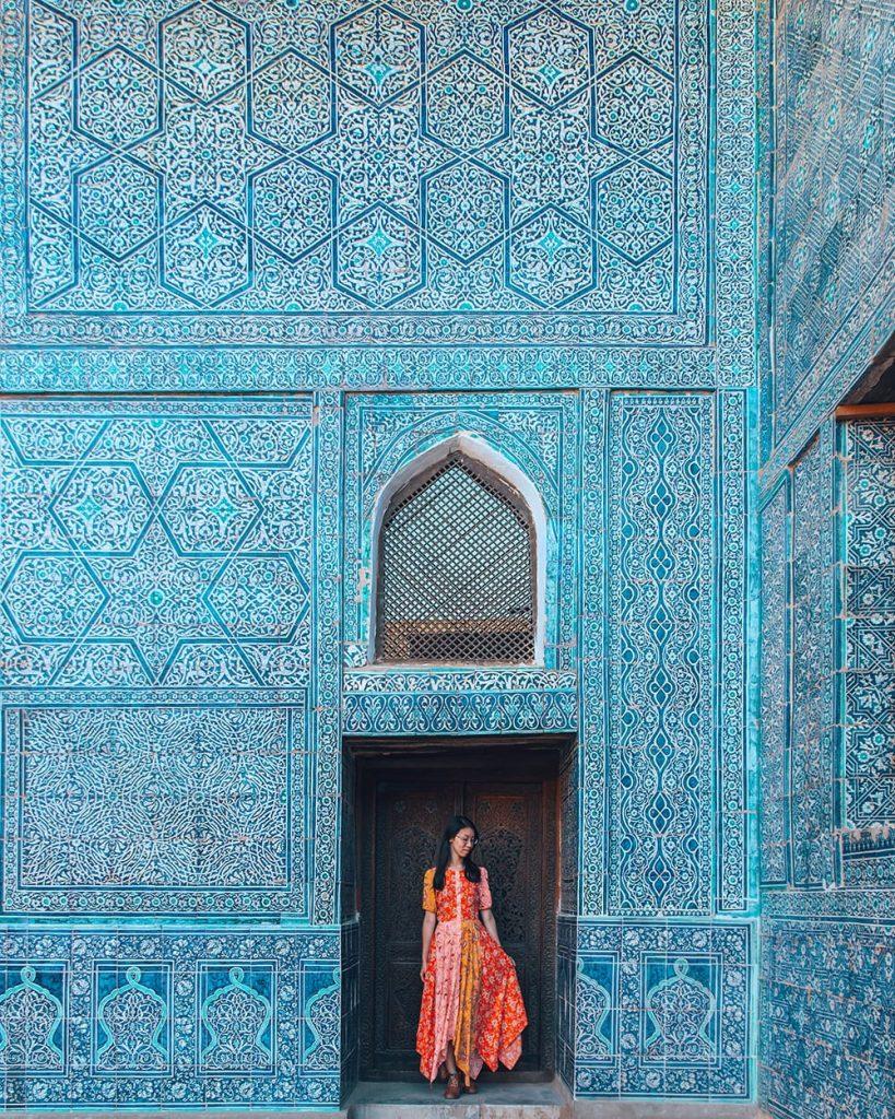 girl standing inside kuhna ark fortress tile work in uzbekistan