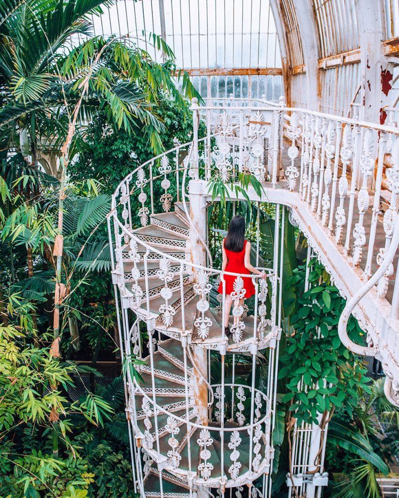 girl standing on staircase of botanical garden in kew gardens in london